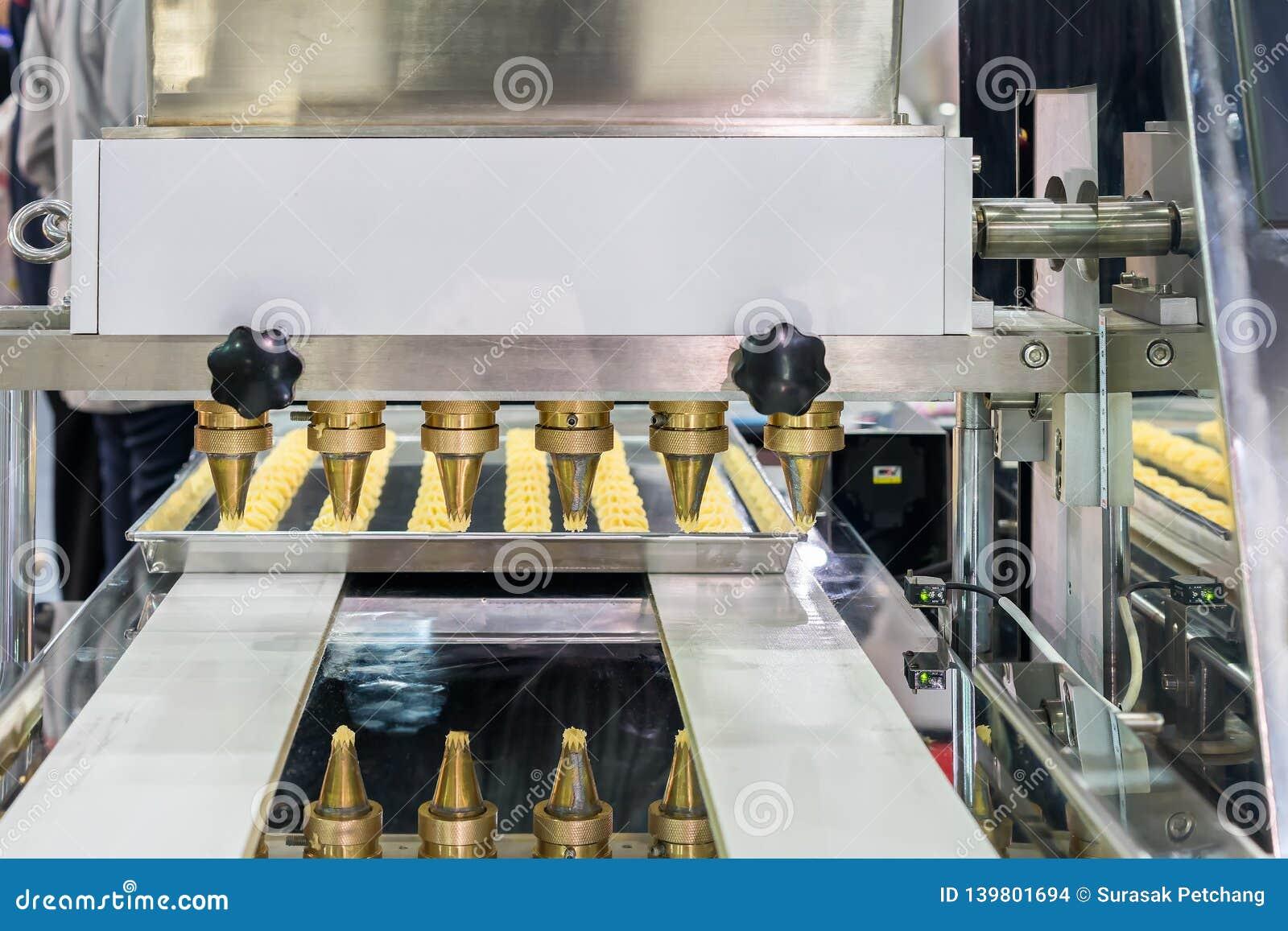 Feche acima da massa ou do creme e proveja de bocal a descarga do biscoito ou dos doces automáticos que fazem a máquina na linha