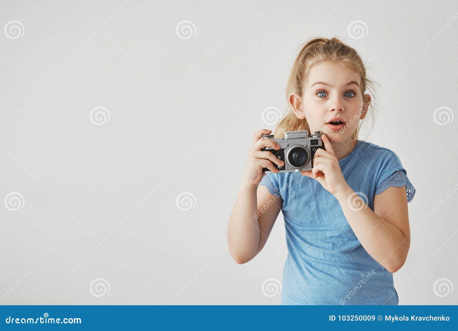 Feche acima da menina bonito pequena com cabelo leve no t-shirt azul que olha in camera com expressão surpreendida da cara, guard