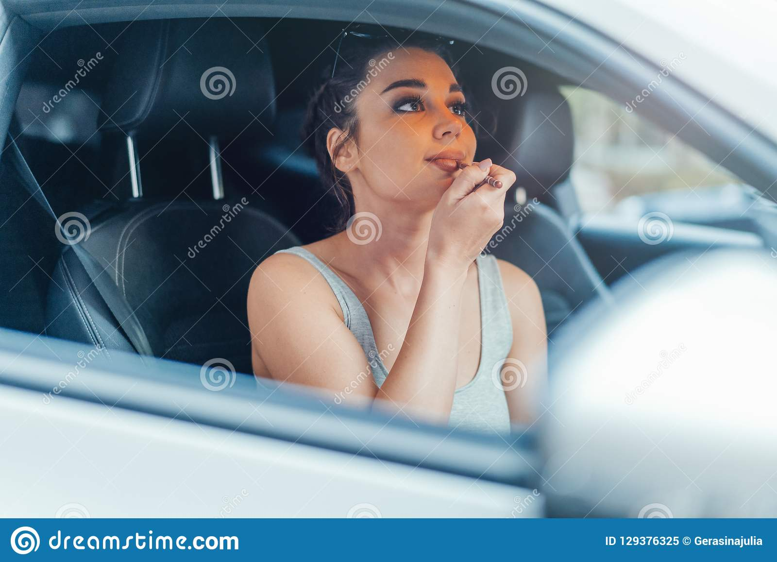 Feche acima da mulher bonita que obtém seus bordos pintados ao sentar-se no carro