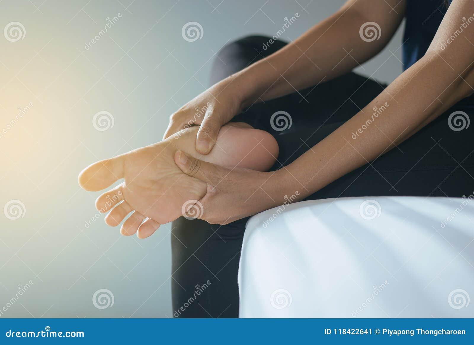 Feche acima da mulher das mãos que tem uma única dor do pé, sentimento fêmea esgotado e doloroso