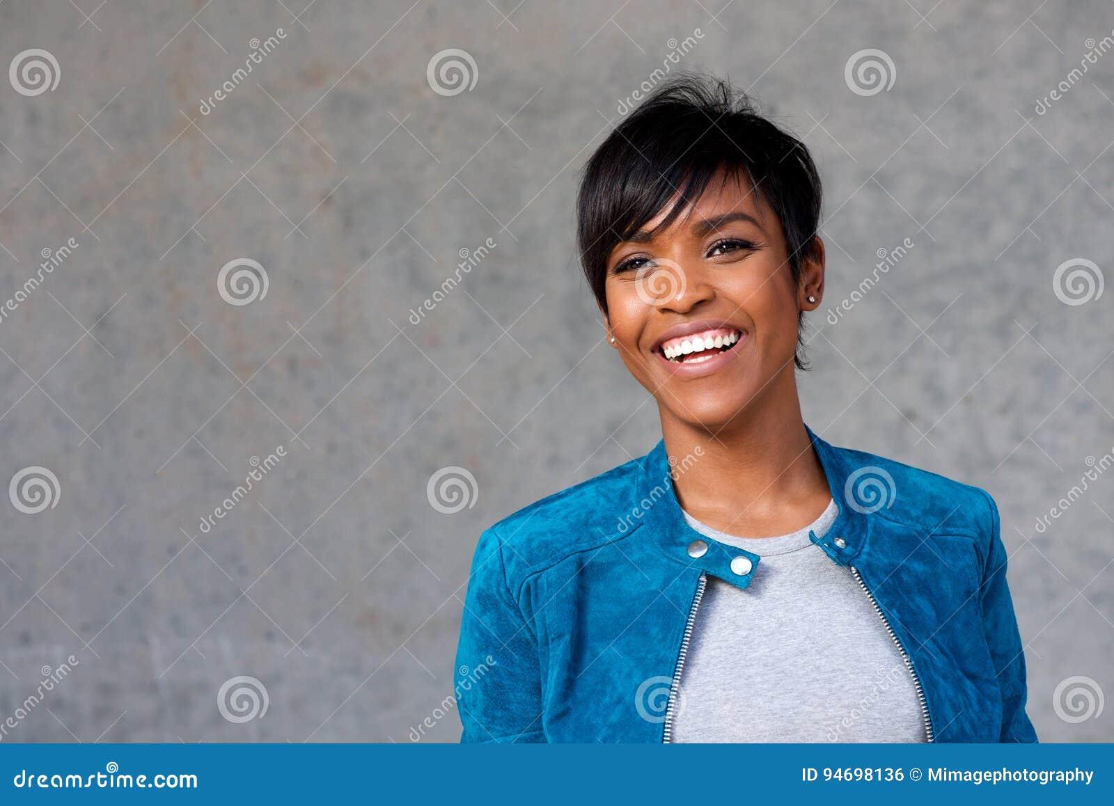 Feche acima da mulher negra nova bonita com sorriso do casaco azul