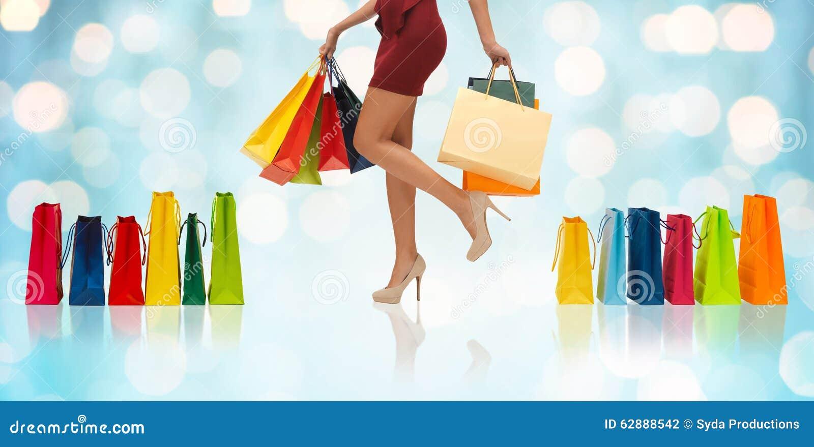 Feche acima da mulher nos saltos altos com sacos de compras