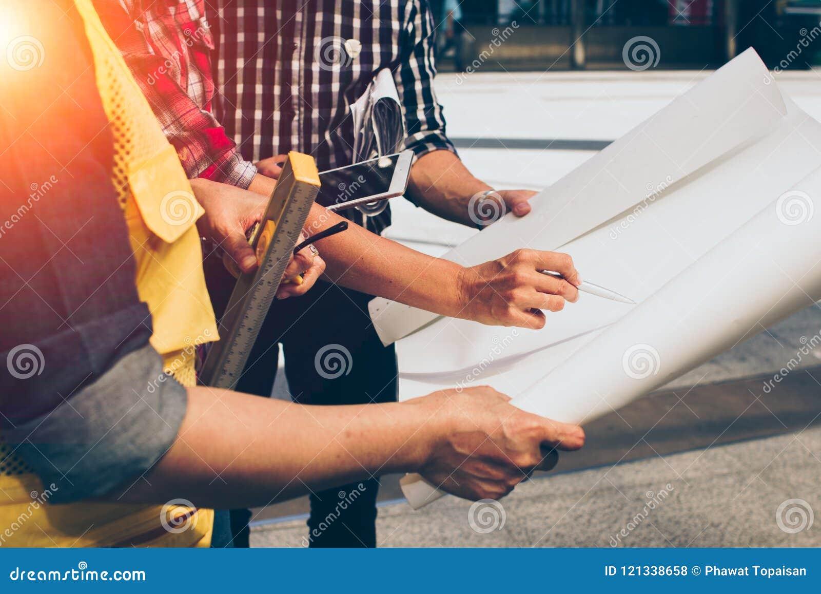 Feche acima da reunião do coordenador da mão para o funcionamento de projeto arquitetónico com as ferramentas do sócio e da engen
