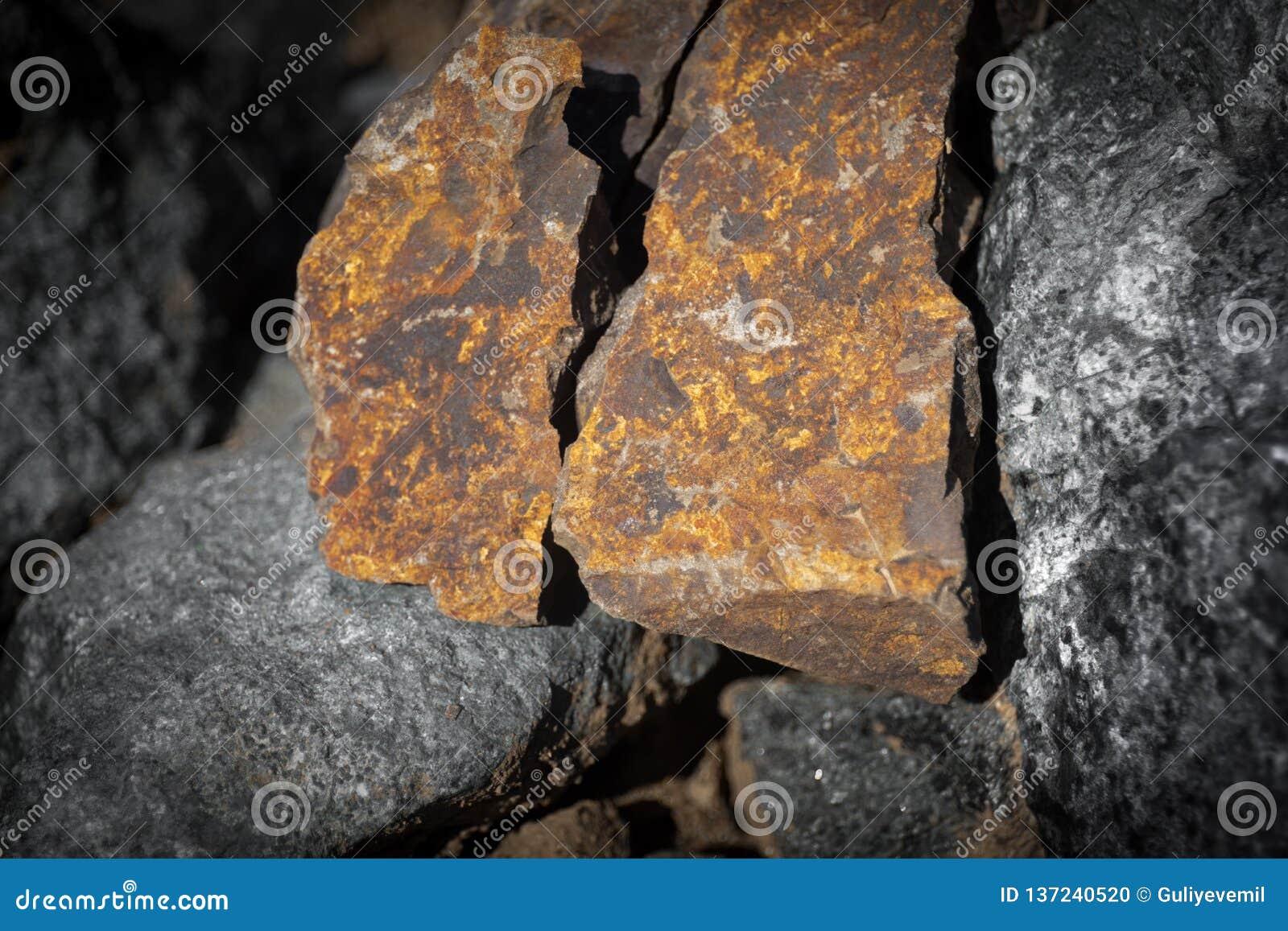 Feche acima da vista exterior da pedra na terra Parte de pedra rochosa alaranjada Textura bonita