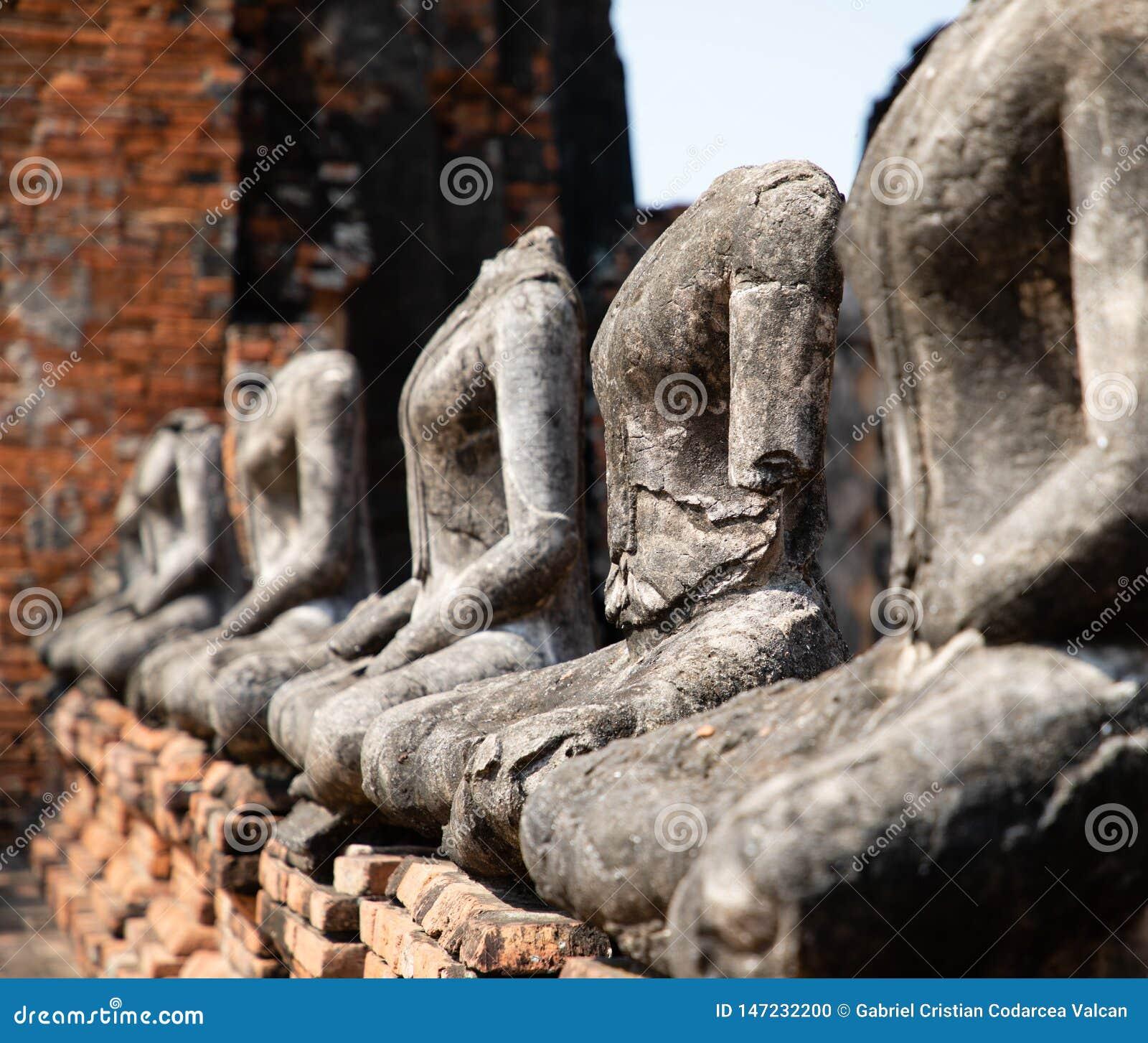 Feche acima das estátuas antigas de buddha da pedra colocadas na linha no templo arruinado em Ayutthaya