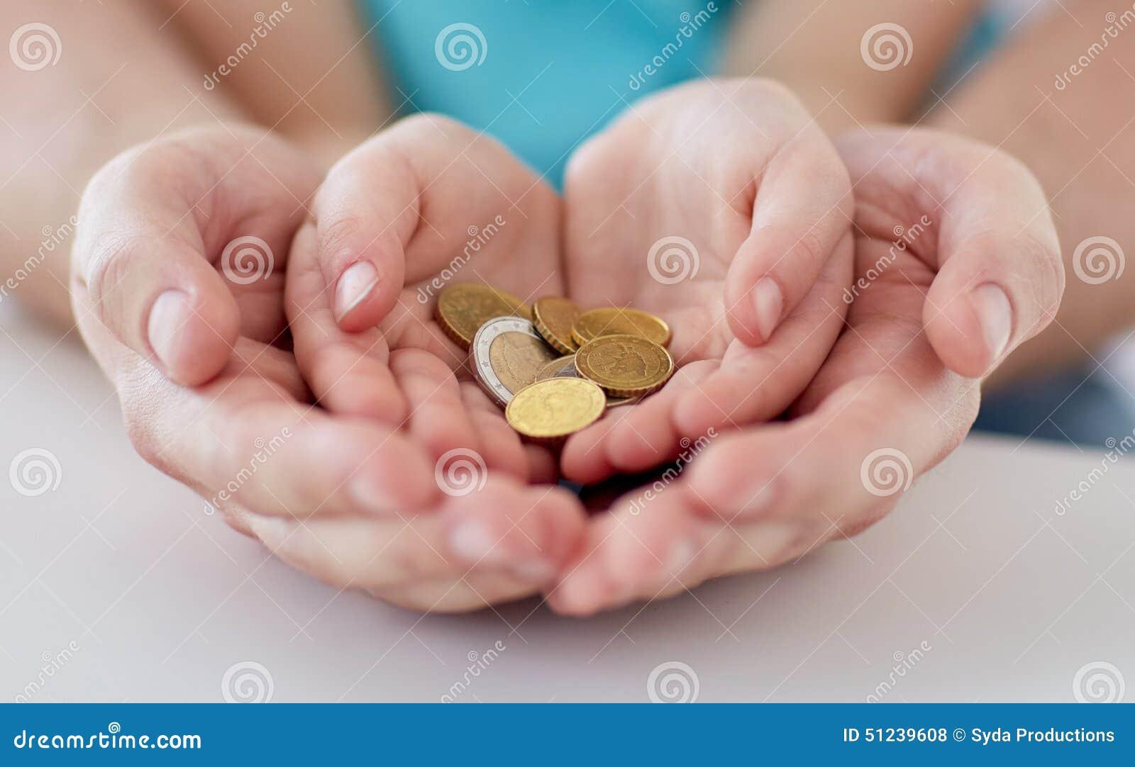 Feche acima das mãos da família que guardam euro- moedas do dinheiro