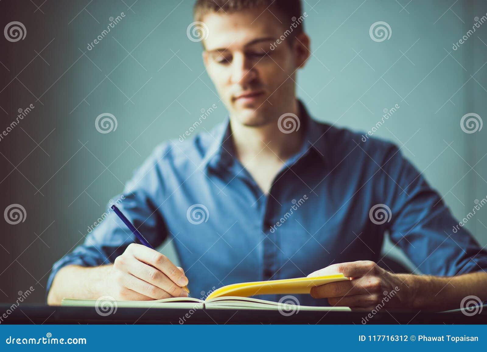 Feche acima das mãos de um homem de negócios em uma camisa azul que assina ou que redige um original em uma folha do caderno