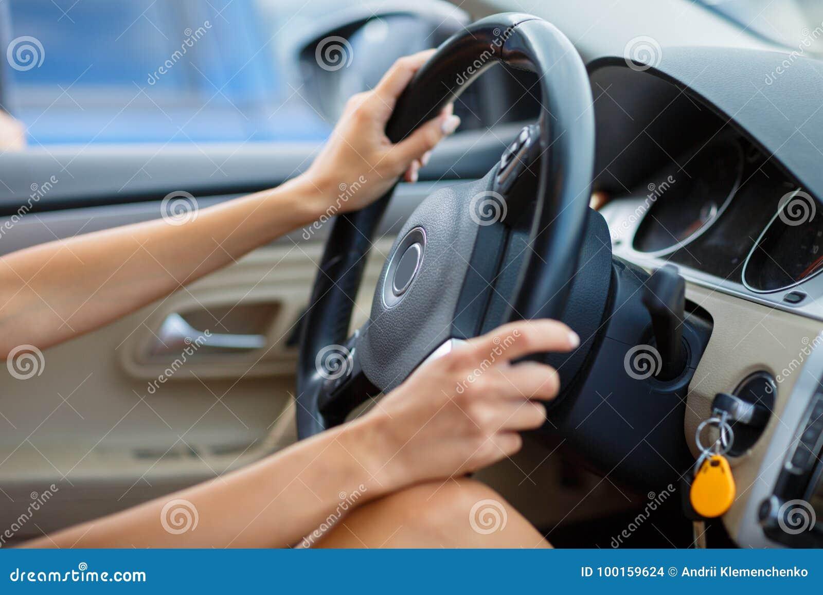Feche acima das mãos do ` s da mulher que guardam o volante