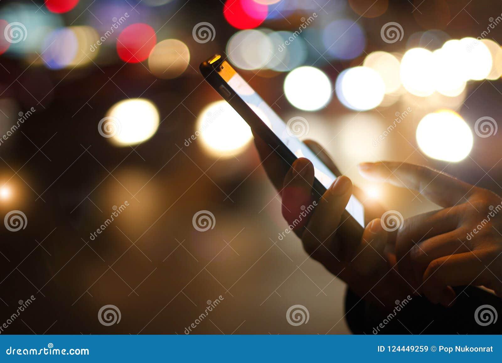 Feche acima das mãos fêmeas usando o smartphone móvel no colo iluminado