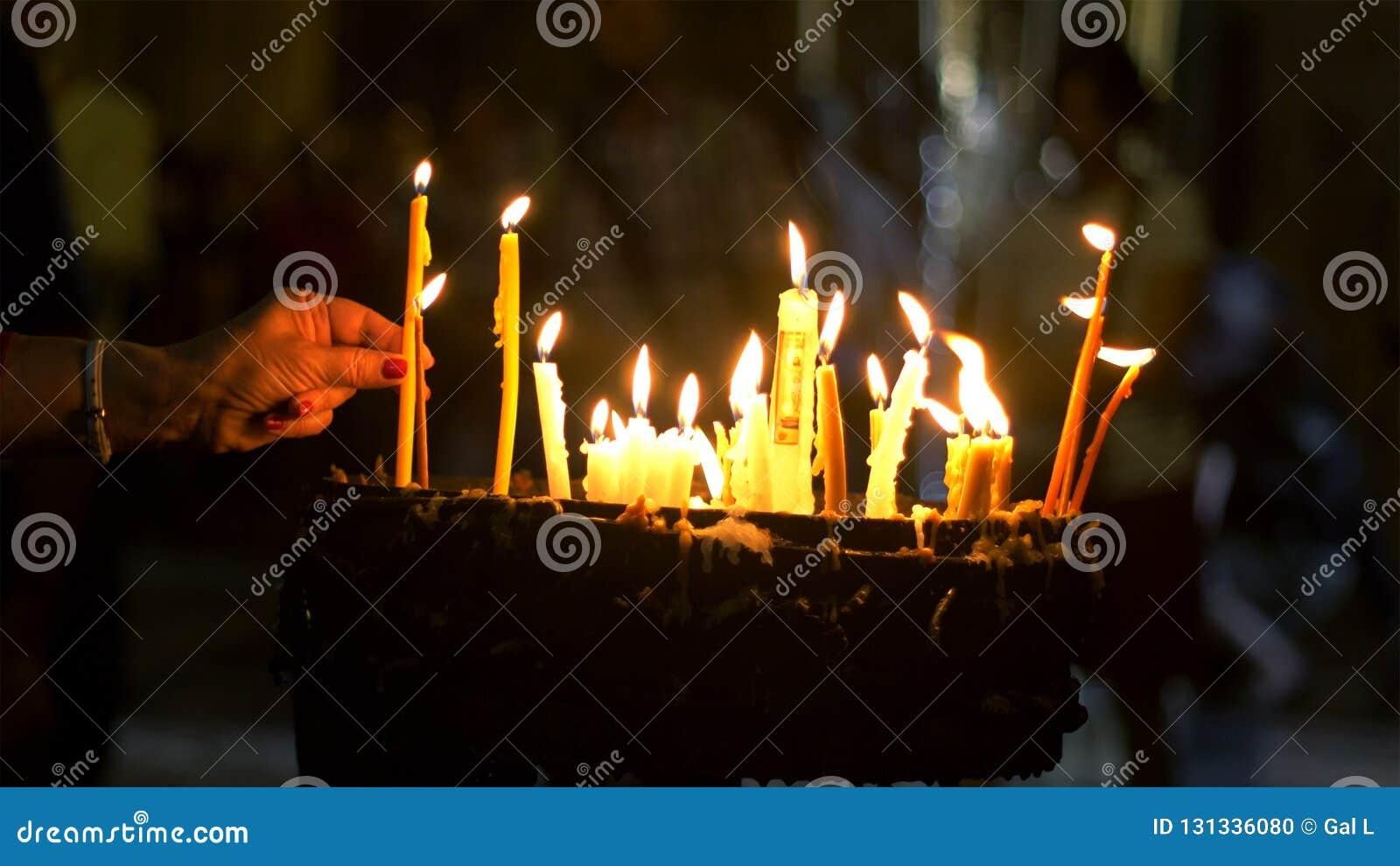 Feche acima das mãos das orações que leve velas na igreja santamente do sepulcro no Jerusalém