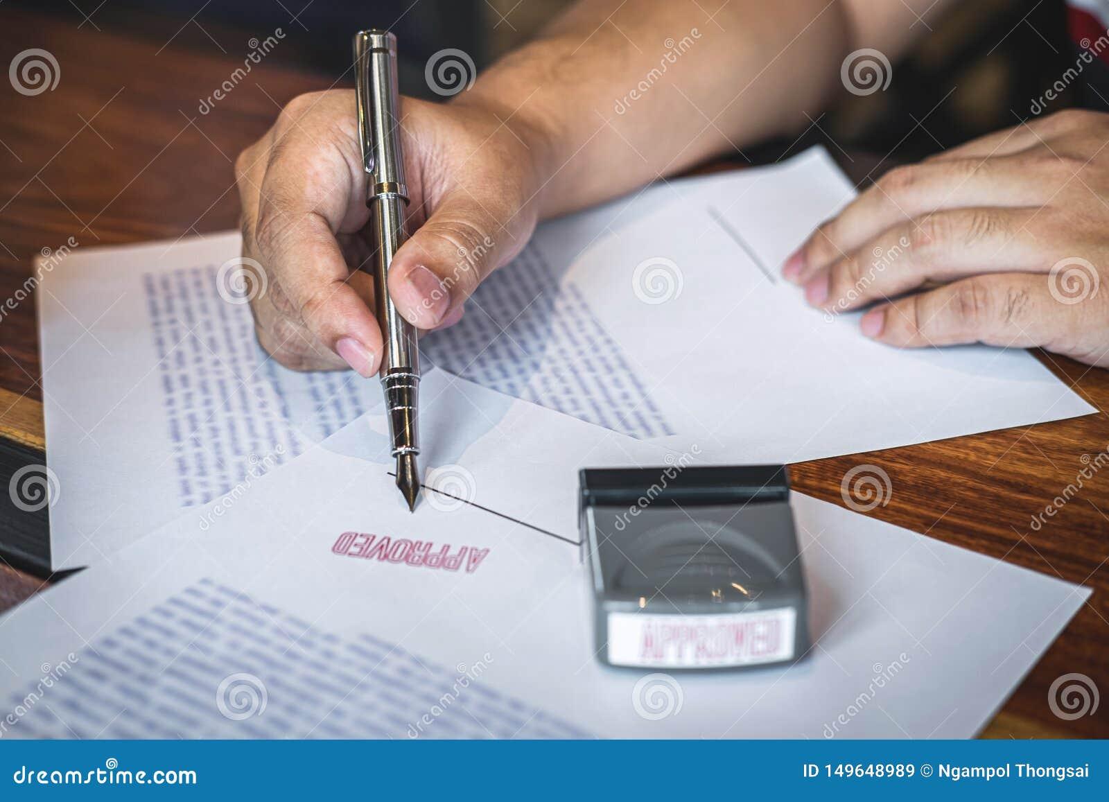 Feche acima das m?os da assinatura e do selo do homem de neg?cios no documento de papel para aprovar o acordo de contrato do inve