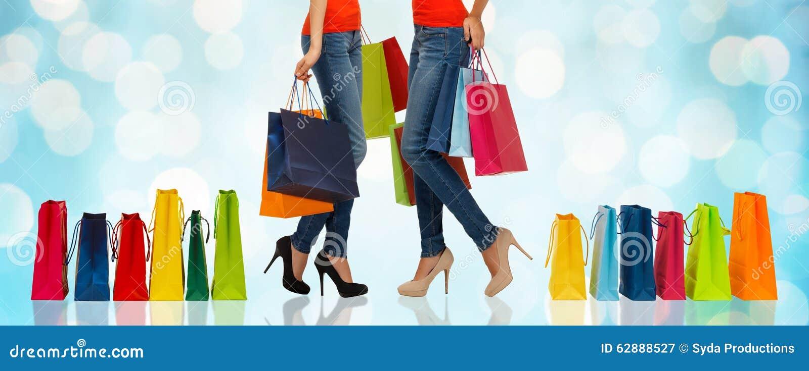Feche acima das mulheres com sacos de compras