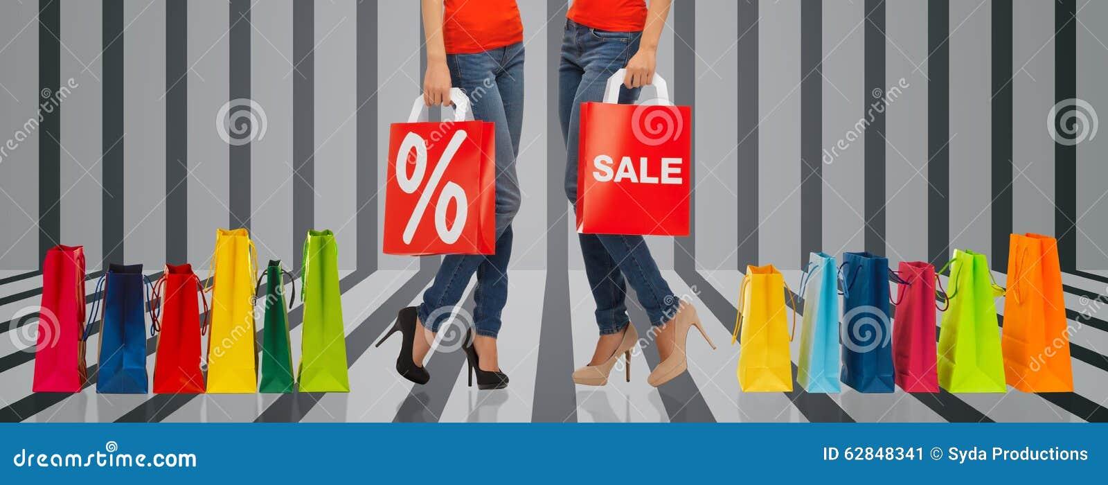 Feche acima das mulheres com sinal da venda no saco de compras