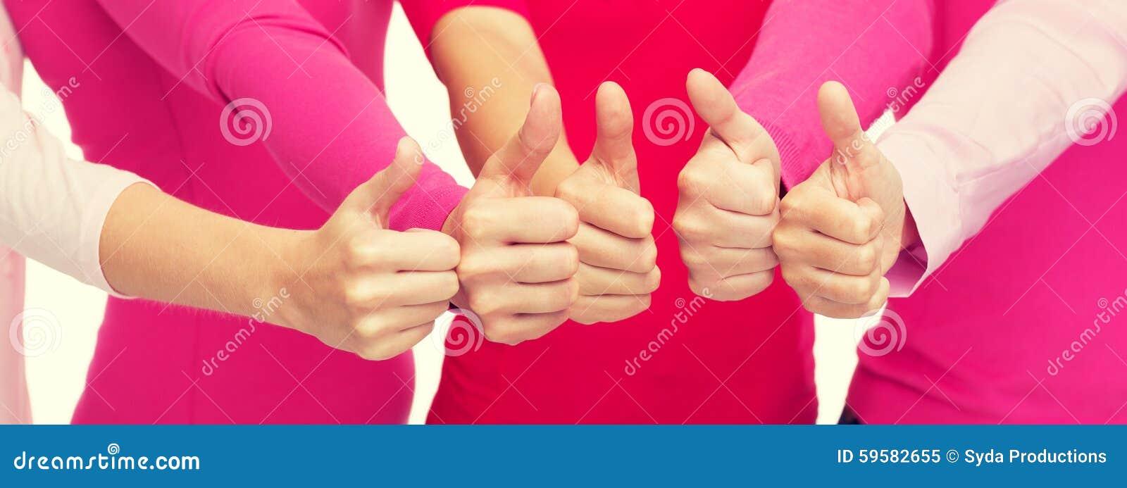 Feche acima das mulheres nas camisas cor-de-rosa que mostram os polegares acima