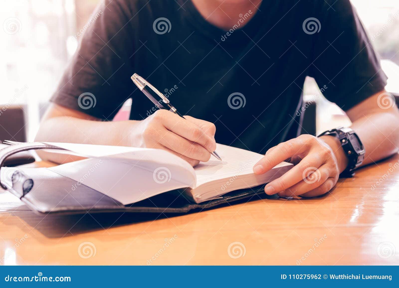 Feche acima das notas novas da escrita da mão na sala de estudo