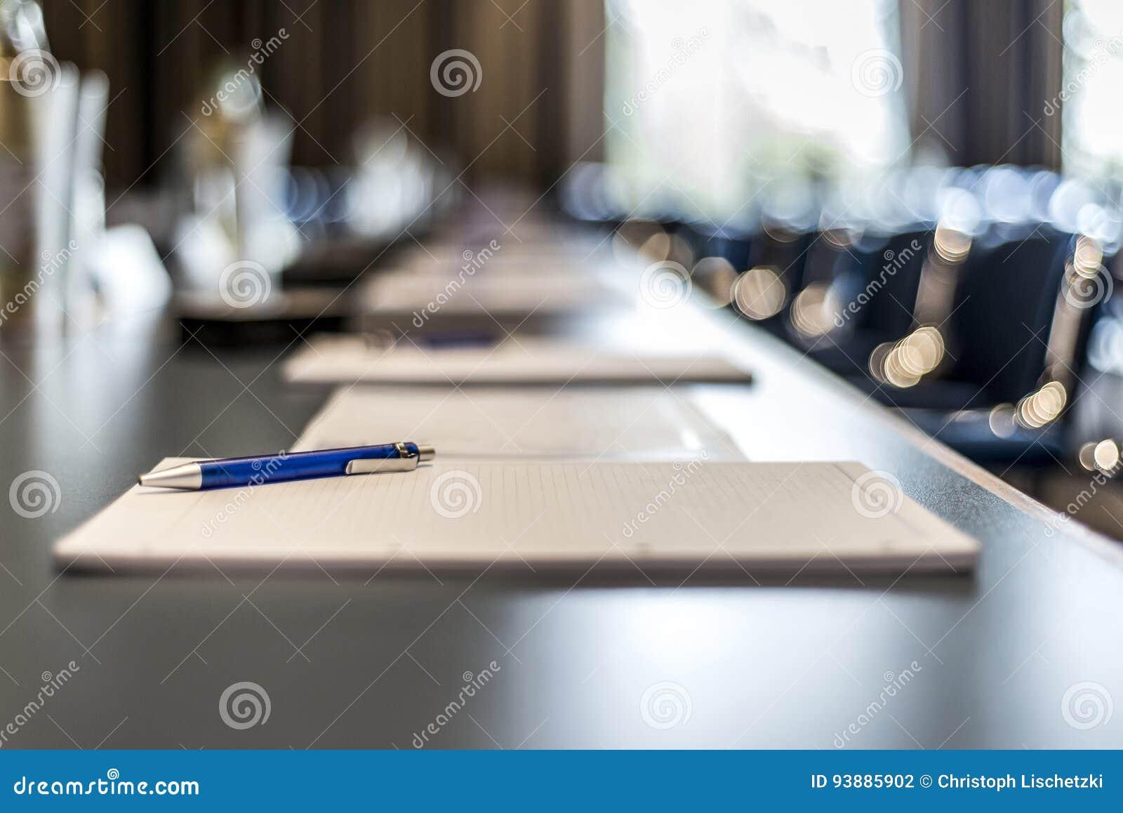 Feche acima das penas escuras dos vidros de água da tabela da conferência, das folhas de papel e do fundo obscuro da janela