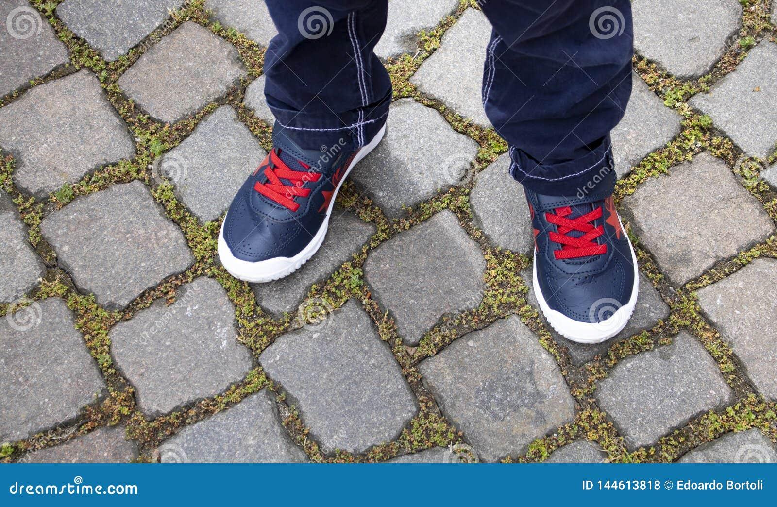 Feche acima das sapatas de uma criança