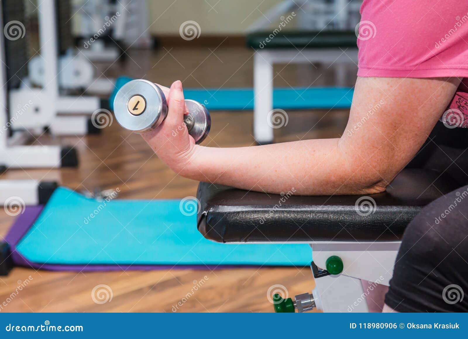 Feche acima de nenhuma mulher superior da cara que faz os exercícios especiais ativos, trabalhando com pesos no gym no centro de
