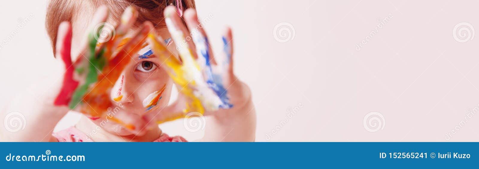 Feche acima de pouca menina bonito com a composição colorida das crianças que mostra as mãos pintadas Conceito feliz da infância