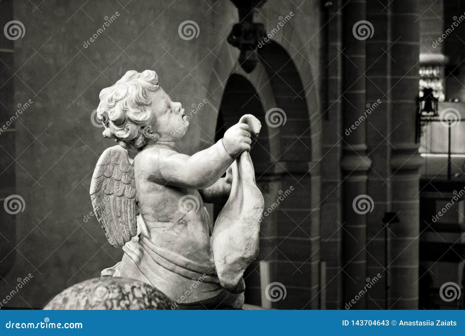 Feche acima de preto e branco de um anjo cinzelado na pedra