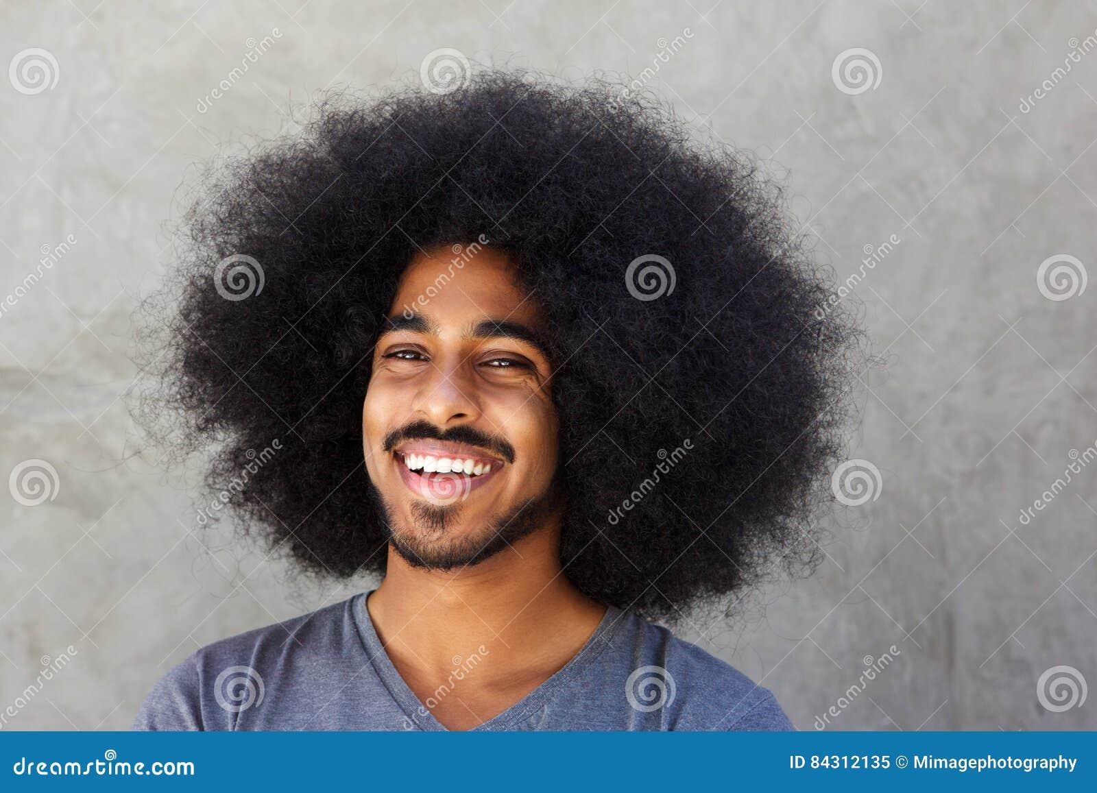 Feche acima de rir o homem afro que está pela parede