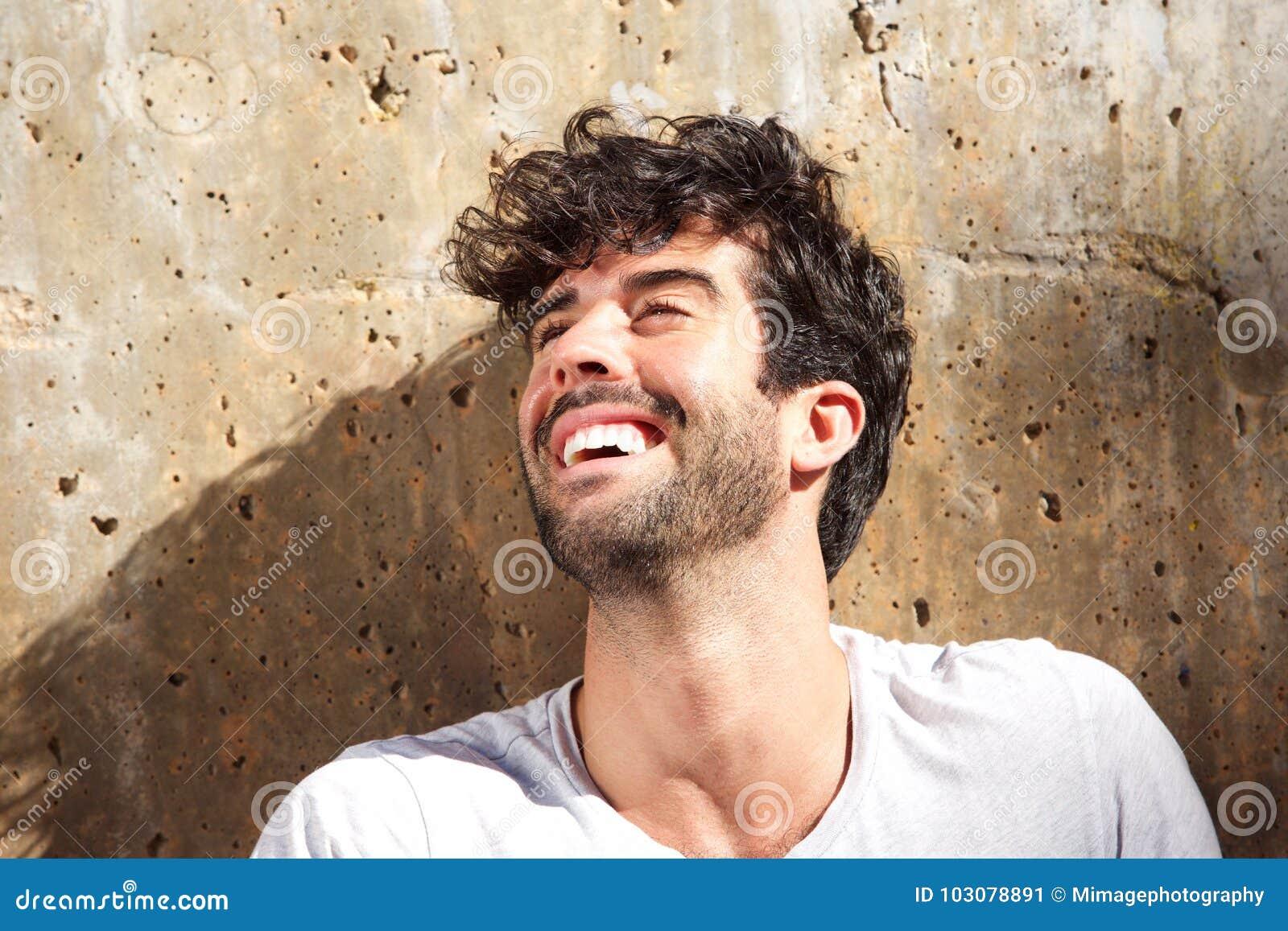 Feche acima de rir o homem despreocupado que senta-se pelo muro de cimento