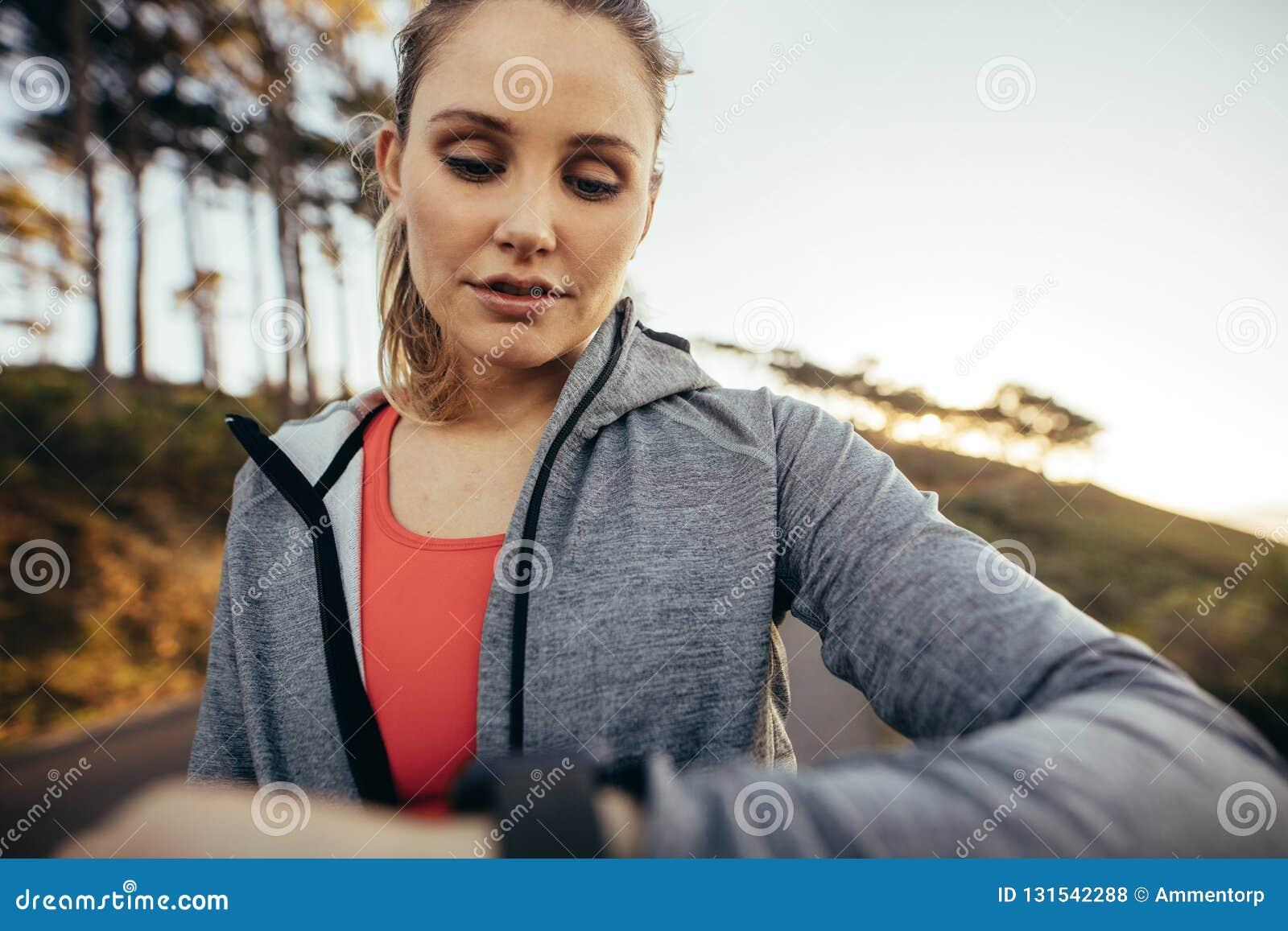 Feche acima de um atleta fêmea que verifica o tempo ao andar na estrada Mulher da aptidão que olha seu relógio de pulso durante s