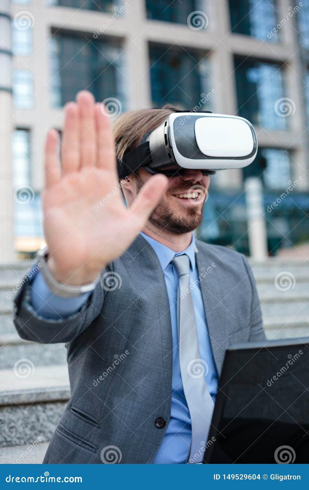 Feche acima de um homem de negócios novo usando óculos de proteção de VR na frente de um prédio de escritórios Conceito do foco s
