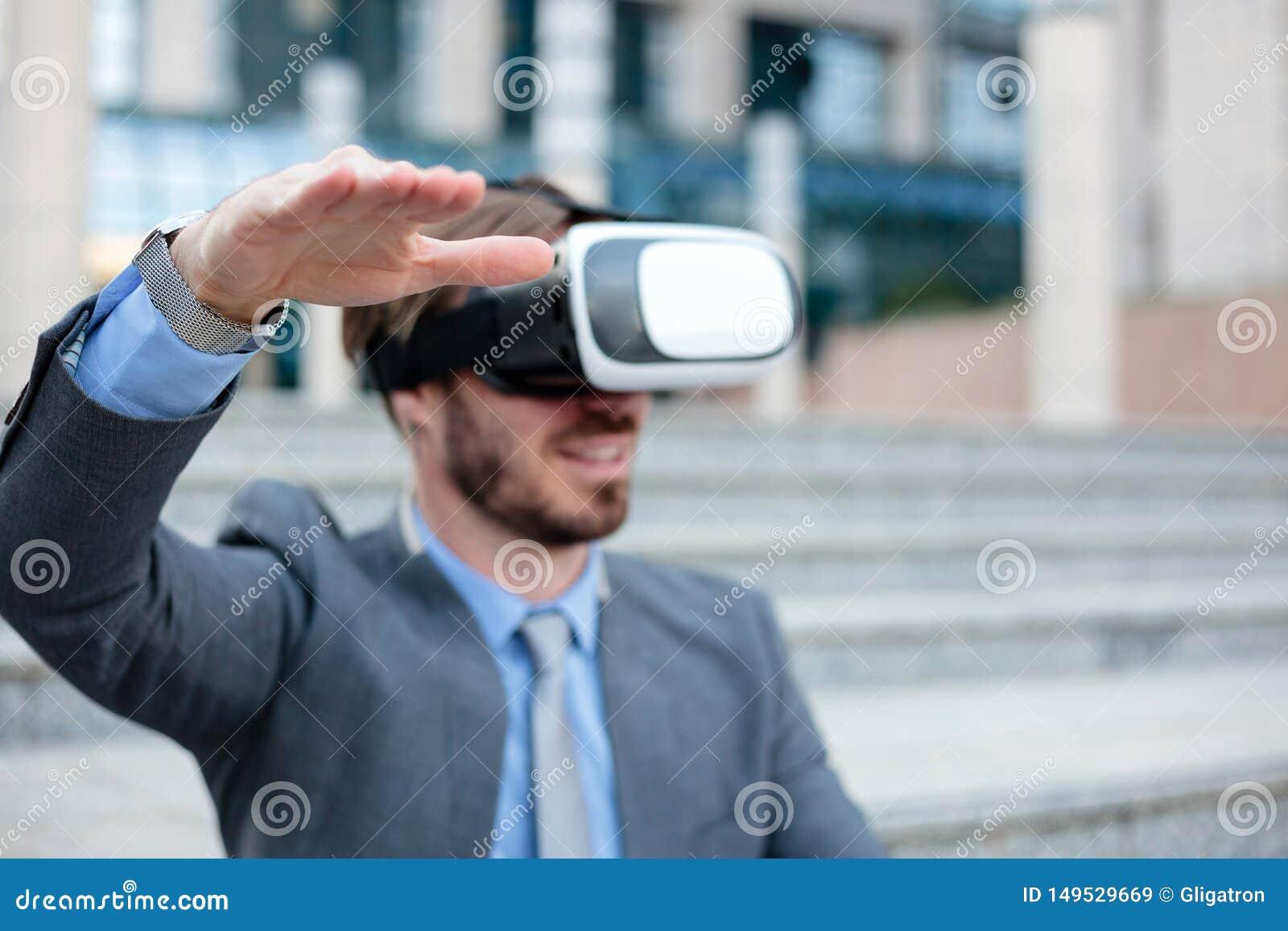 Feche acima de um homem de negócios novo usando óculos de proteção de VR na frente de um prédio de escritórios, fazendo gestos de