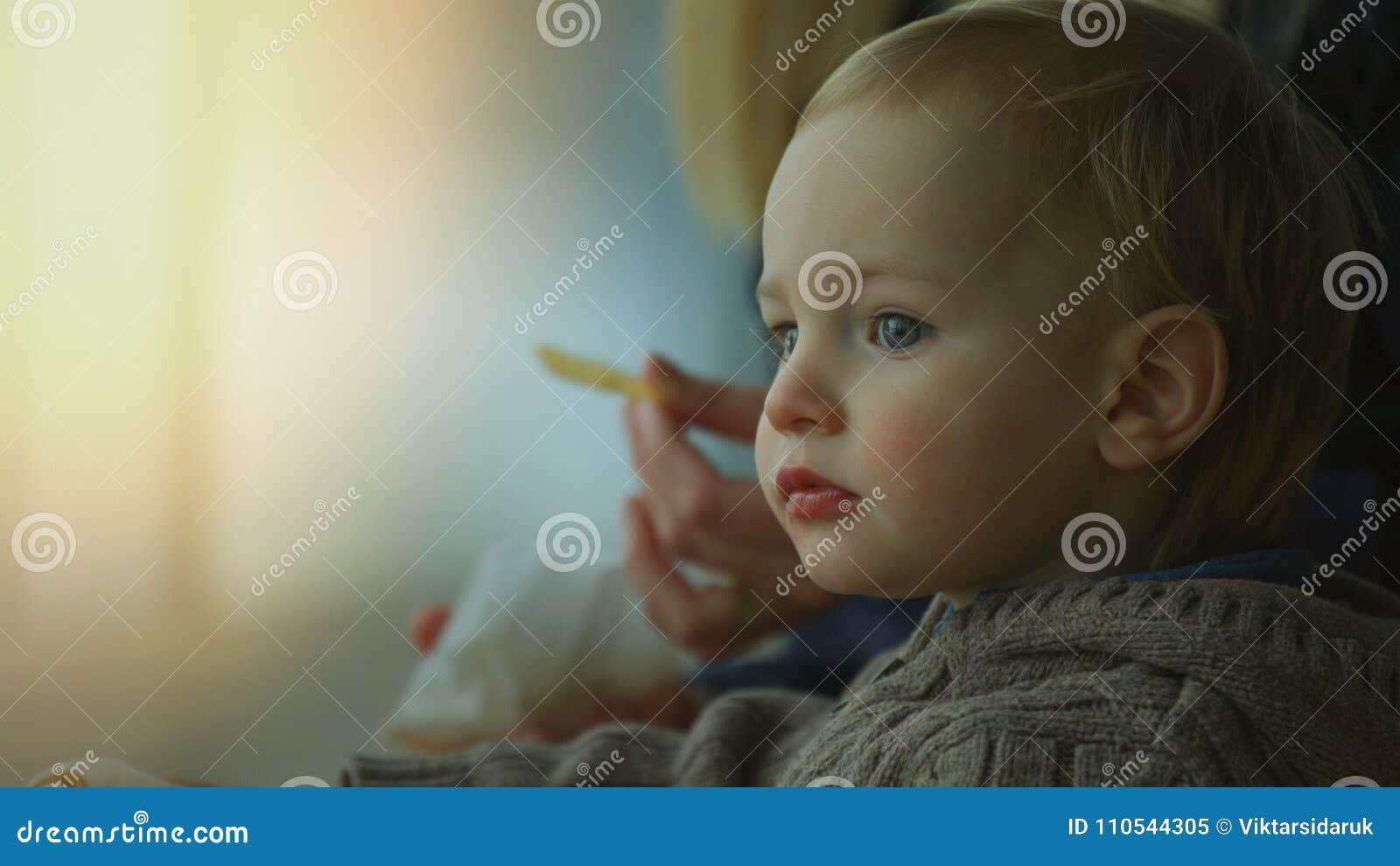 Feche acima de um menino pequeno bonito que come batatas fritas