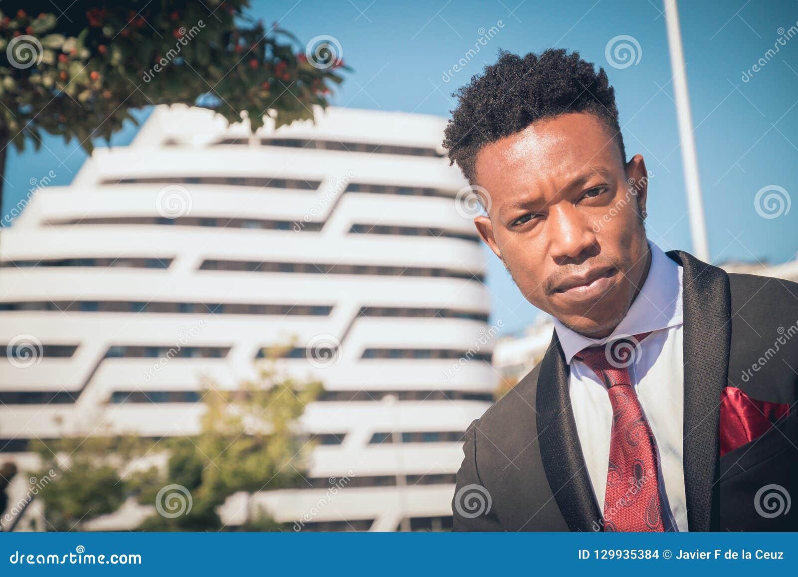 Feche acima de um novo e do homem de negócios preto atrativo que olha a câmera na frente de uma construção moderna na cidade que