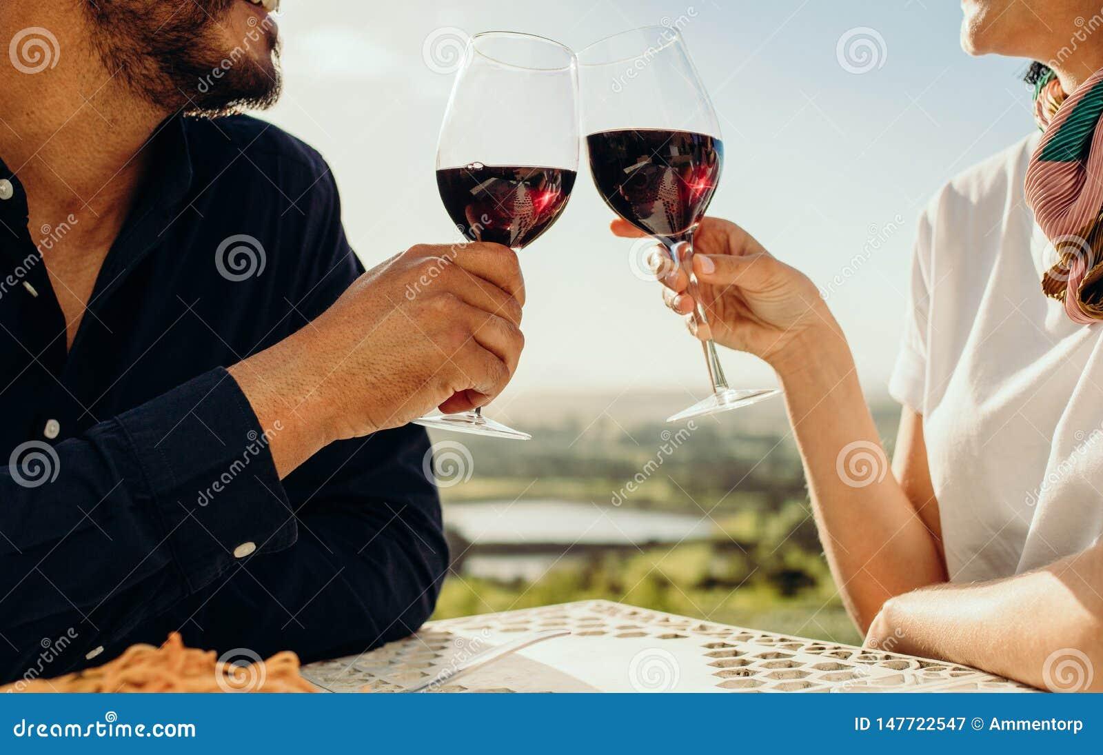 Feche acima de um par que brinda o vinho