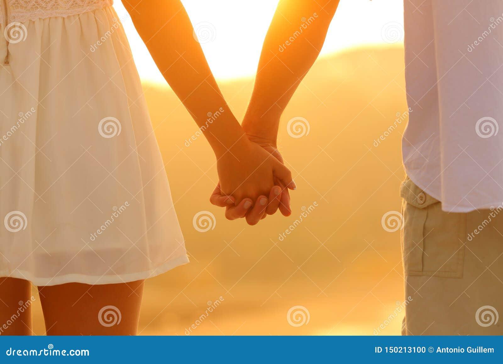 Feche acima de um par que guarda as mãos no por do sol