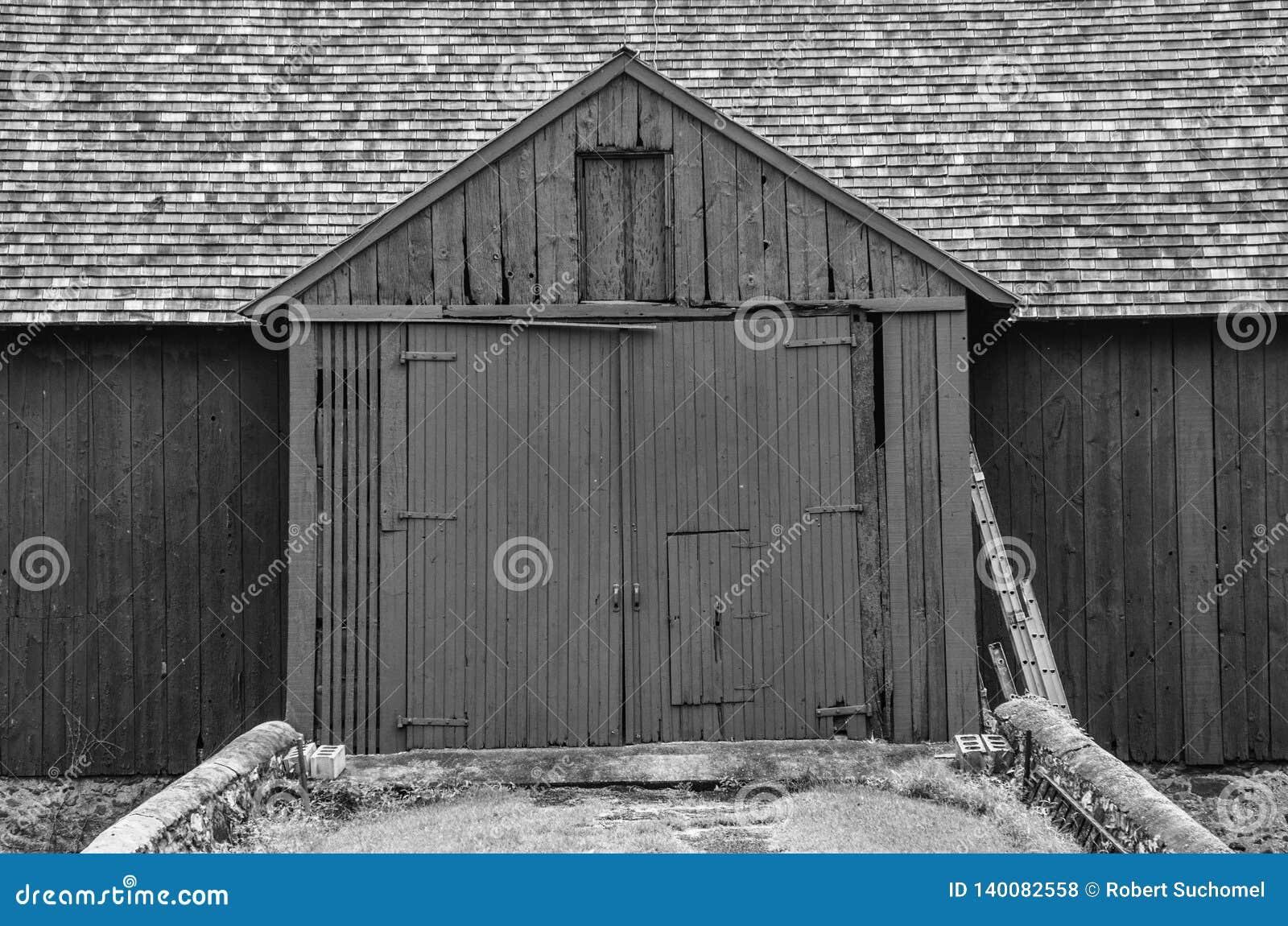 Feche acima de um preto um celeiro branco com as grandes portas dobro
