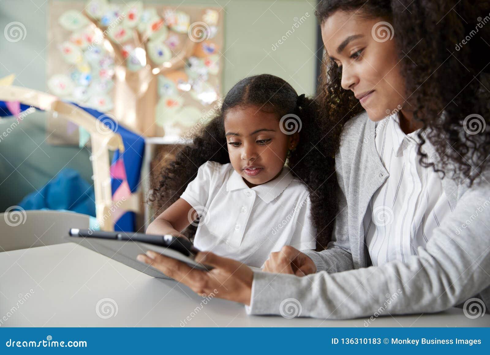Feche acima de uma estudante preta nova que senta-se em uma tabela em uma sala de aula da escola infantil que aprende um em uma c