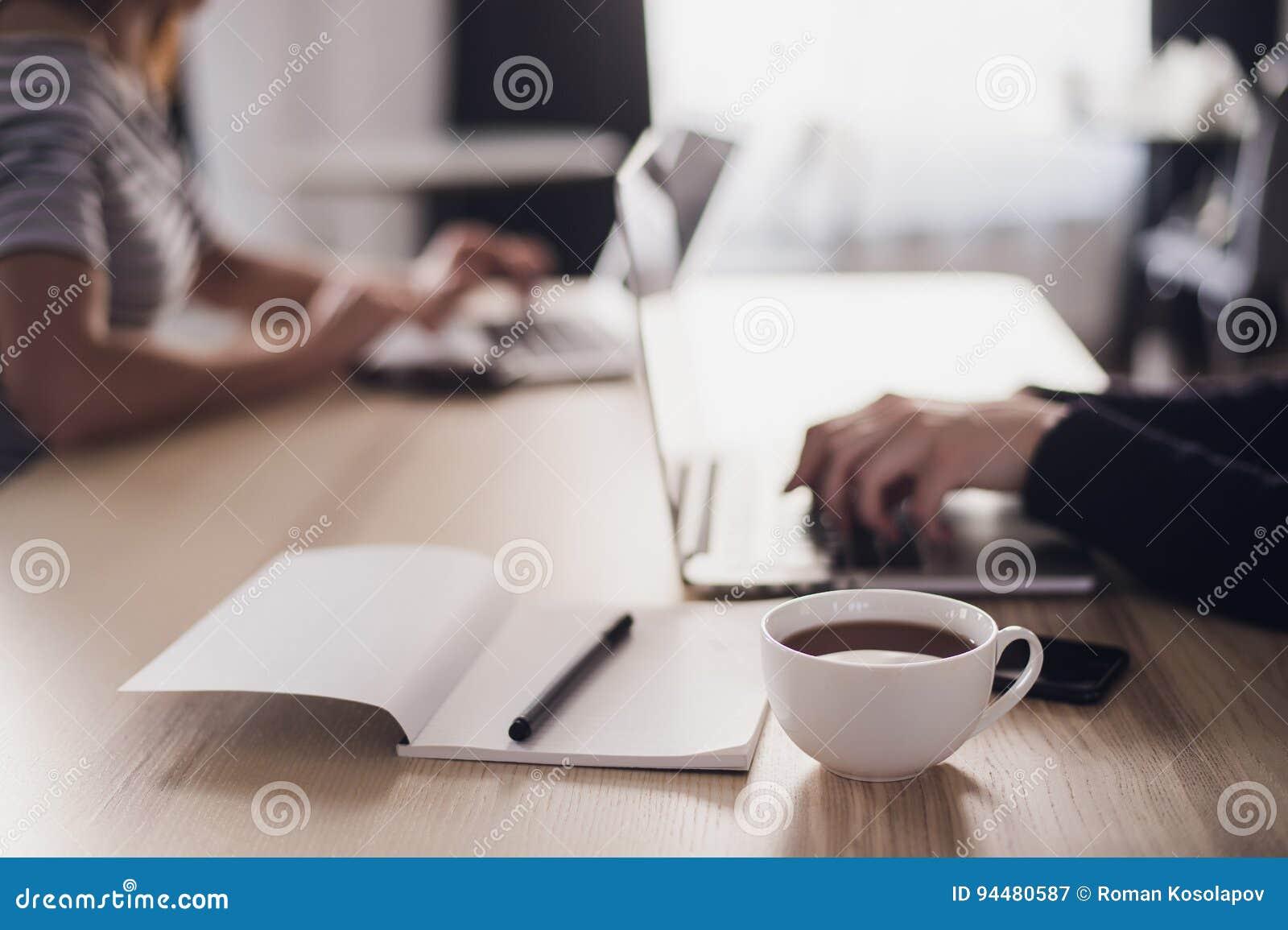 Feche acima de uma imagem de duas mulheres de negócios que usam o tablet pc e o portátil Caderno com pena e xícara de café no