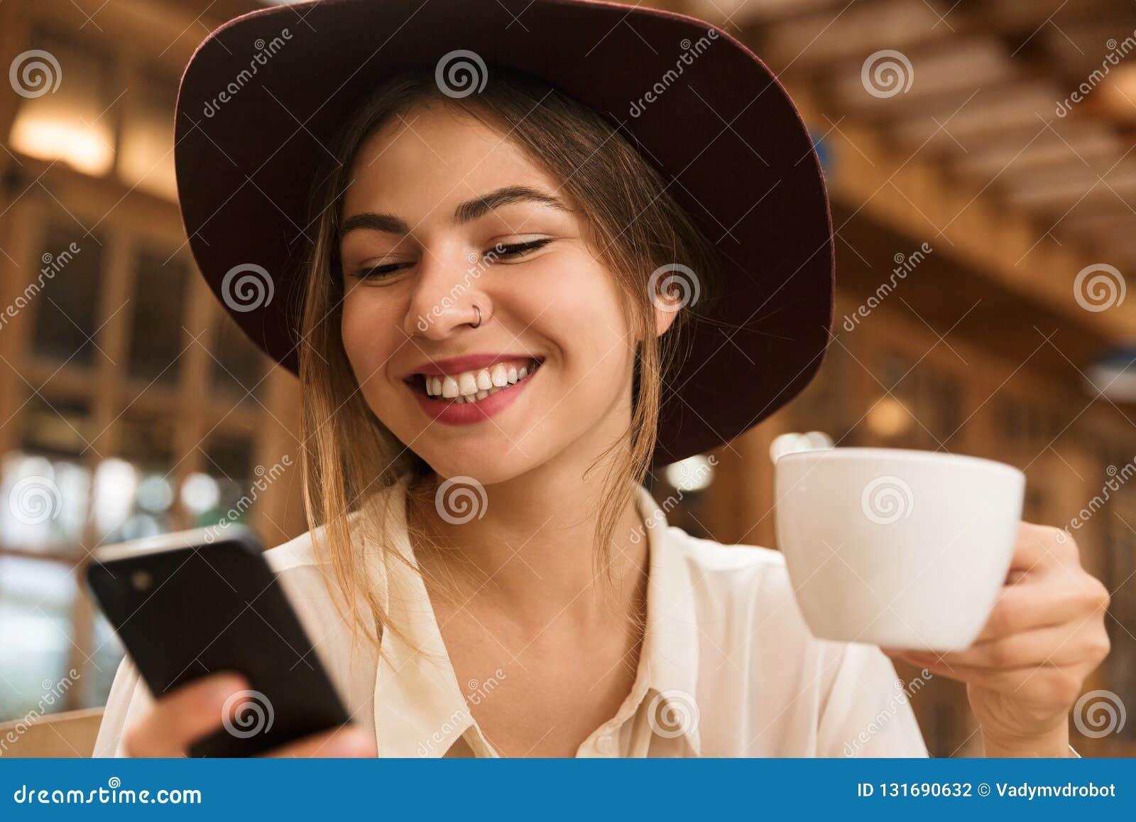 Feche acima de uma menina bonita de sorriso no chapéu que senta-se na tabela do café dentro, guardando o copo do chá,