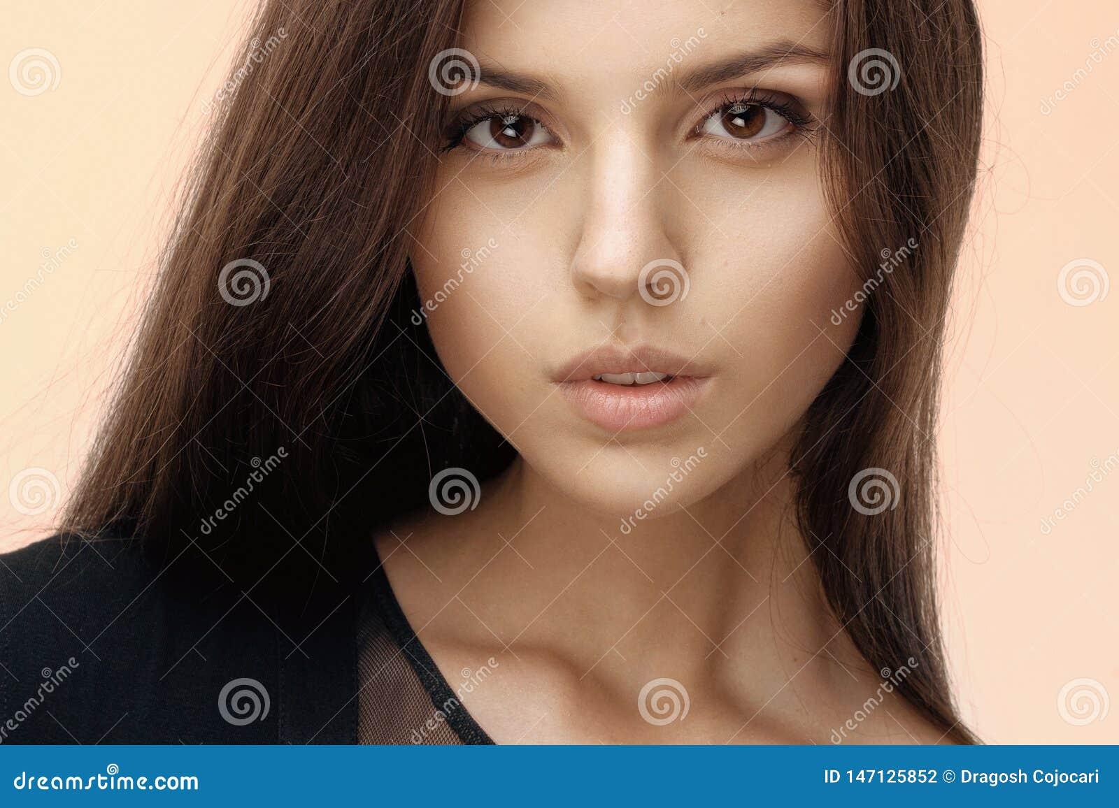 Feche acima de uma menina moreno com sedutor e natural compõe, cabelo longo, olhando a câmera, vestida no preto