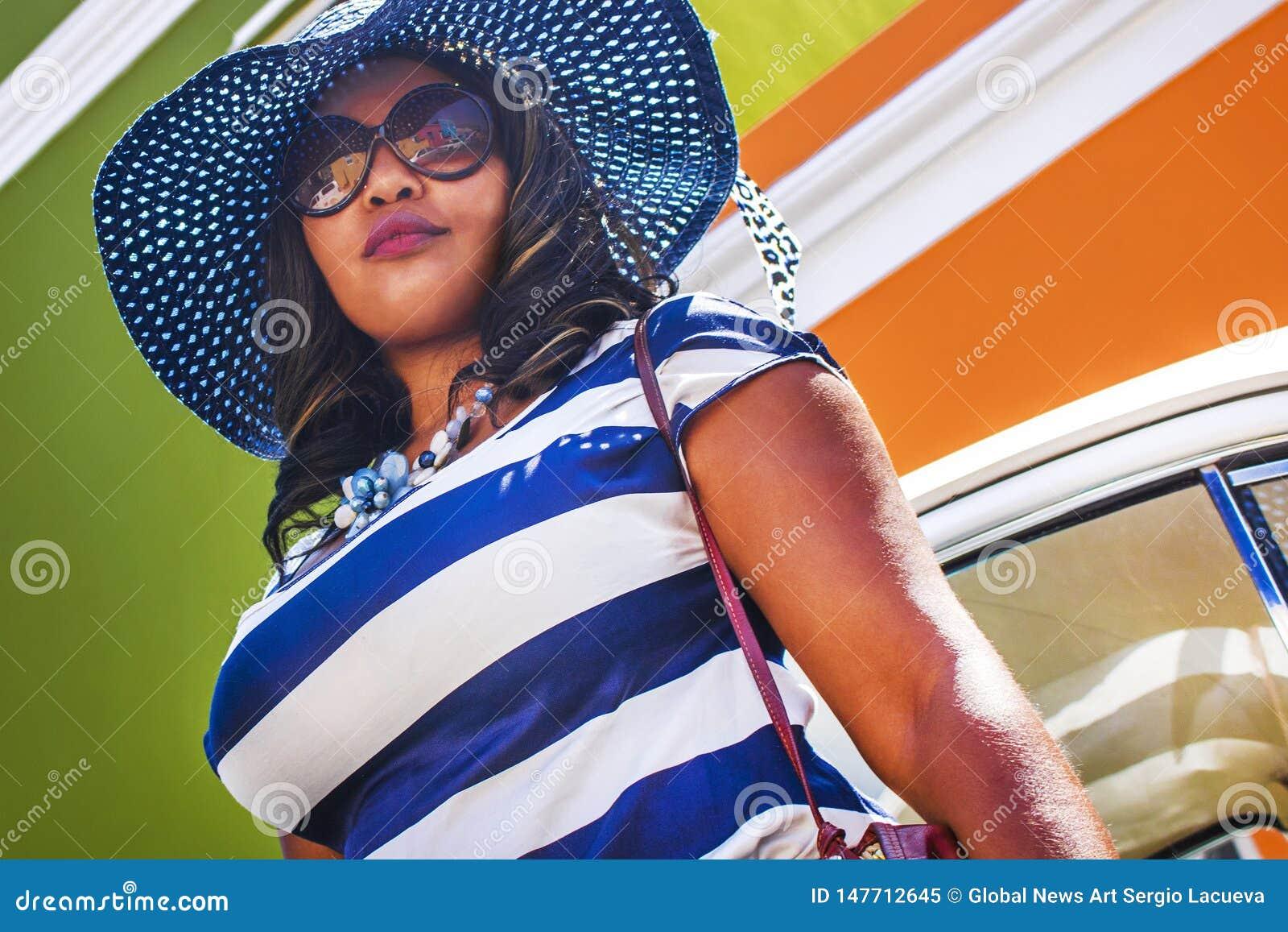 Feche acima de uma mulher africana bonita em um vestido listrado azul e branco na frente de um vintage Volkswagen Beetle e tradic
