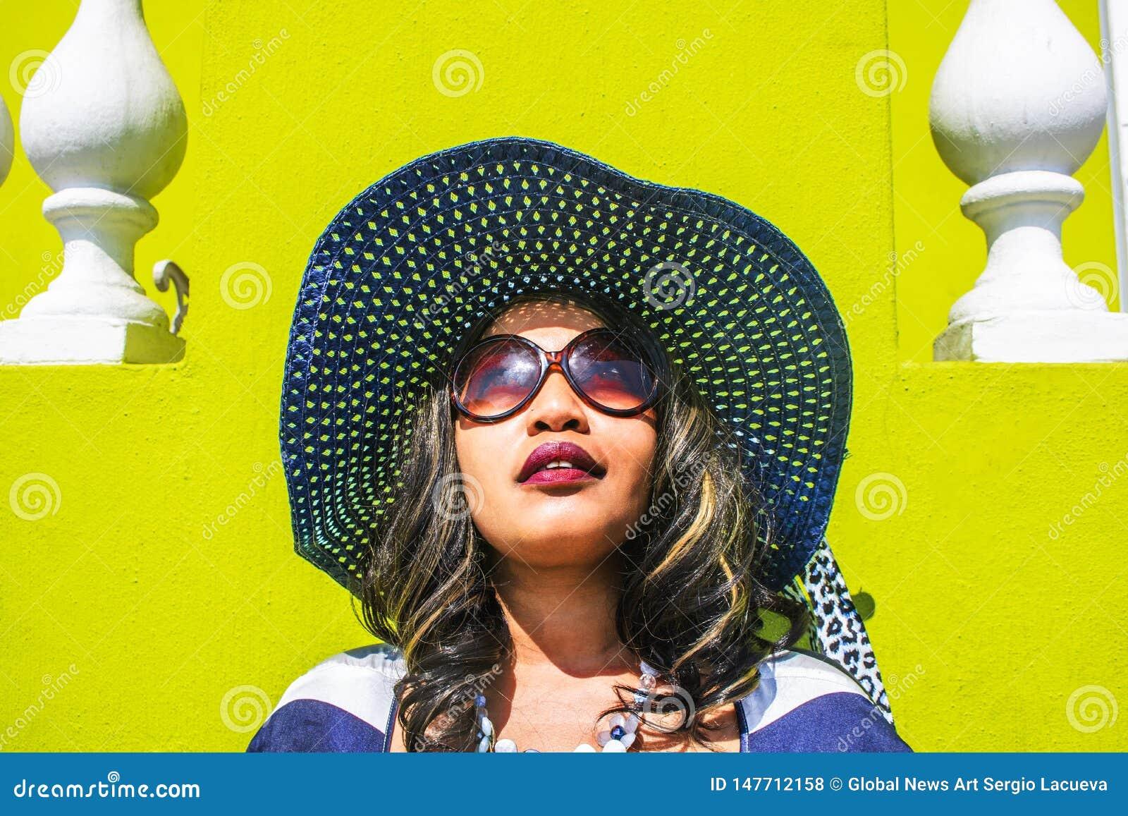 Feche acima de uma mulher africana bonita em um vestido listrado azul e branco que modela na frente de uma casa BO-Kaap tradicion