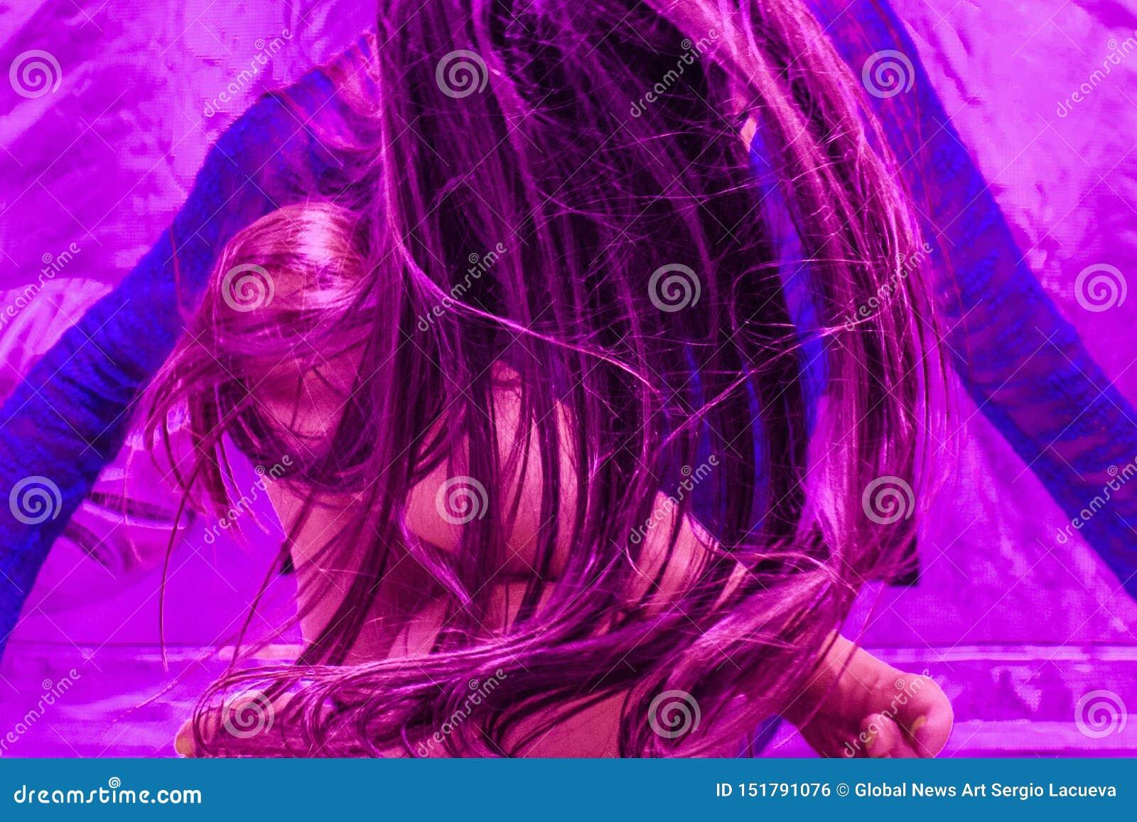 Feche acima de uma mulher bonita em uma parte superior azul de néon e em uns óculos de sol azuis que passam rapidamente seu cabel