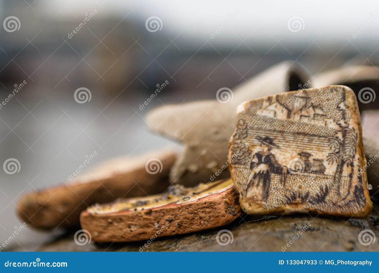 Feche acima de uma parte detalhada de cerâmica quebrada velha encontrou ao longo de um rio