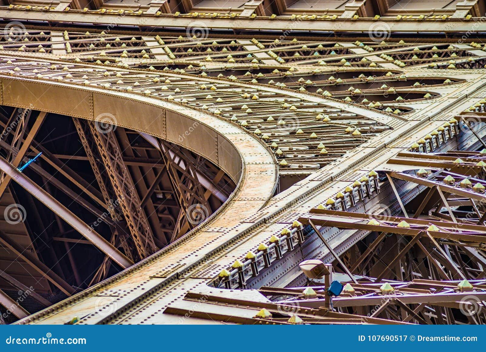 Feche acima do arco e metal fitas da torre de Eifel