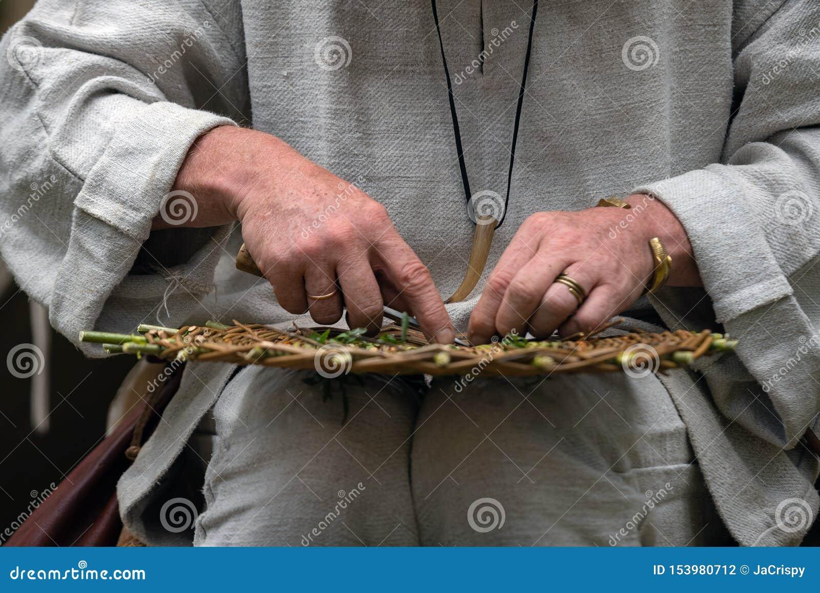 Feche acima do artesão que veste a roupa rural que faz a cesta de vime dos galhos Técnica de tecelagem feito a mão tradicional na