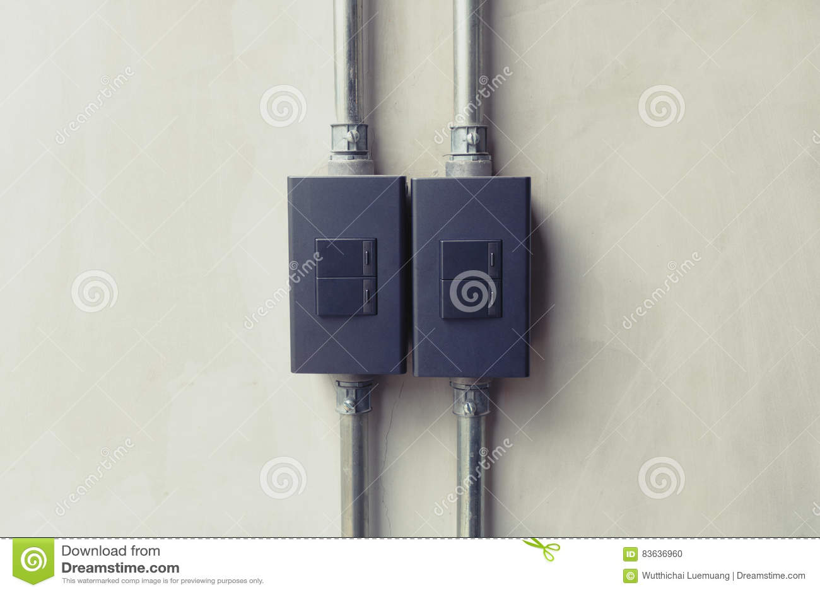 Feche acima do botão de interruptor preto da iluminação no papel de parede concreto b