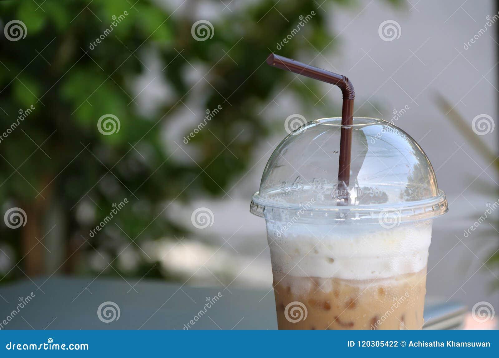 Feche acima do café de gelo no copo plástico com palha marrom e focalize para fora o caderno