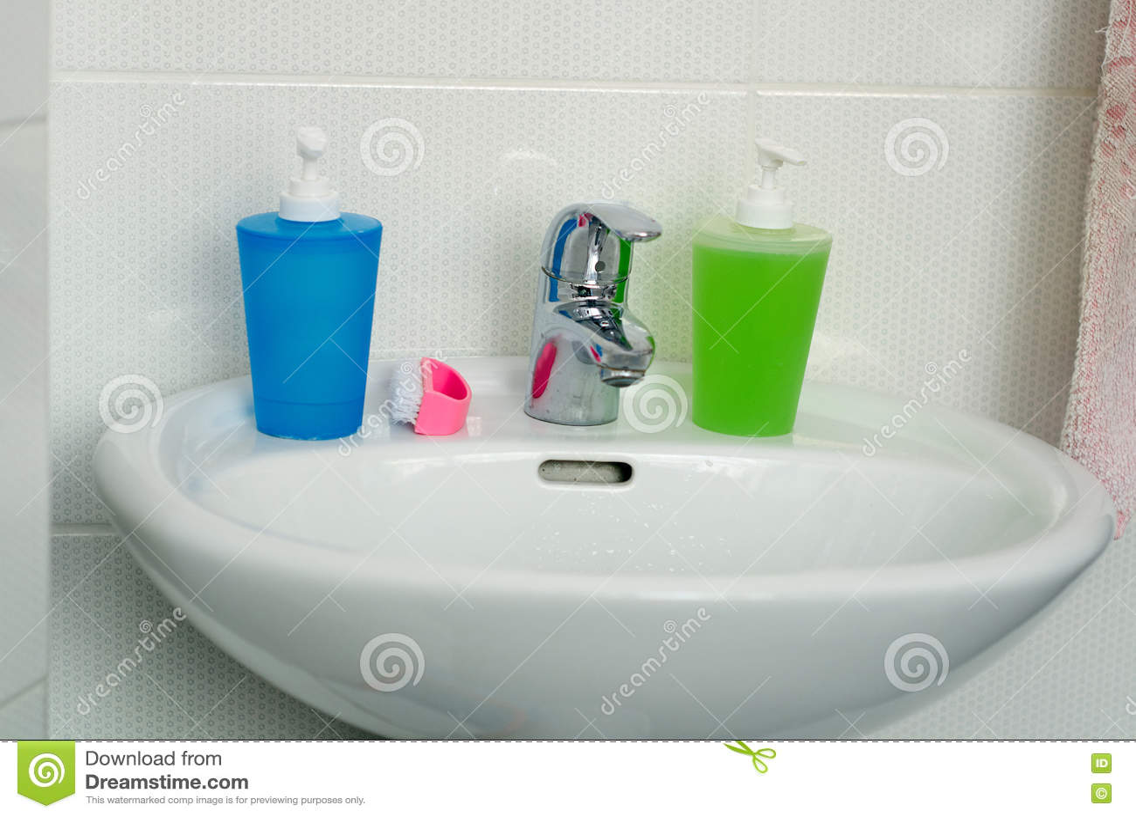 Feche acima do dissipador, da torneira e dos acessórios modernos do banheiro