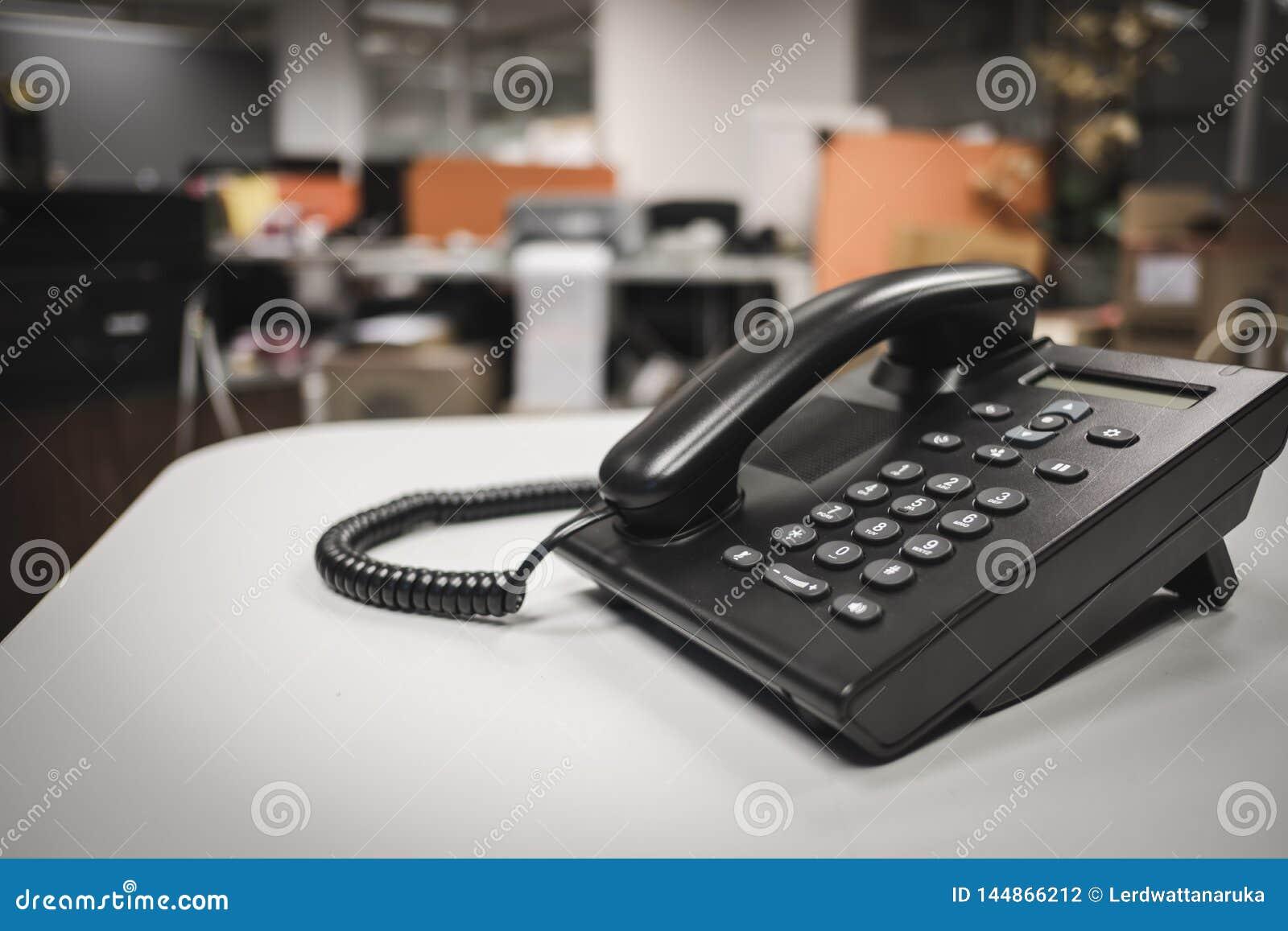 Feche acima do foco macio em dispositivos do telefone do IP com espaço na mesa de escritório