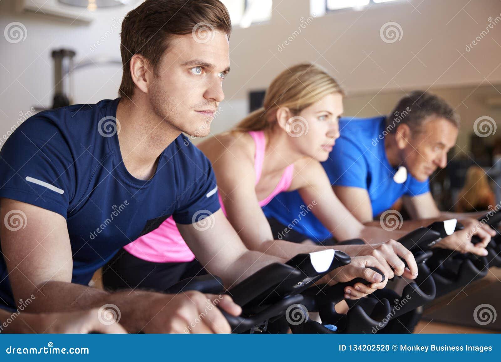 Feche acima do grupo que toma a classe da rotação no Gym