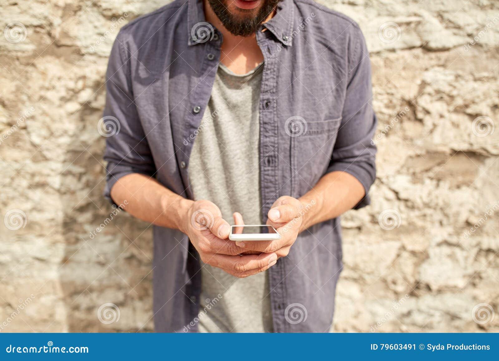 Feche acima do homem com o smartphone na parede de pedra
